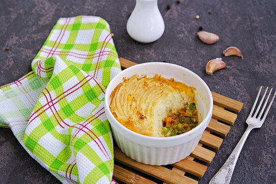 Portion shepherds pie or traditional British potato casserole with minced meat and vegetables on a dark brown concrete background. Potato Recipes. Copyspace.