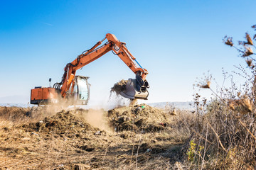 Excavator clears land for construction of a highway Fotomurales