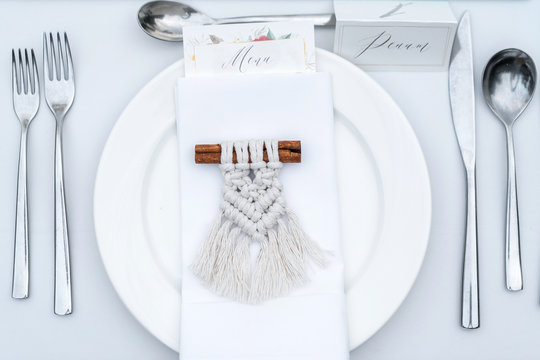 Name card on a plate and a gift to guests of Macrame on a stick of cinnamon. Decorative item for a wedding dinner.
