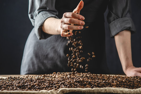 Hand pouring fragrant coffee beans on a pile of roasted Arabica grains. Selection of fresh coffee for espresso