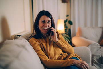 woman sitting sofa at home talking on mobile phone