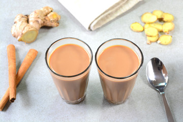 Ginger cinnamon masala tea prepared and served in glass tea cups.