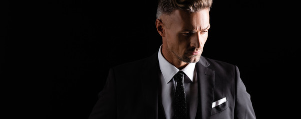 Panoramic shot of handsome businessman looking away isolated on black