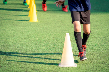 Young soccer player is training with sport cone marker on green grass football pitch training ground