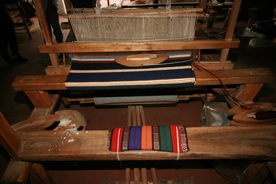 Old fashioned loom with woven blanket in progress