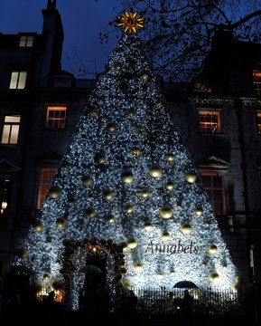 Pedestrians shield themselves from the rain as they walk past a huge Christmas tree design display covering the front of a members club in Mayfair, London, Britain