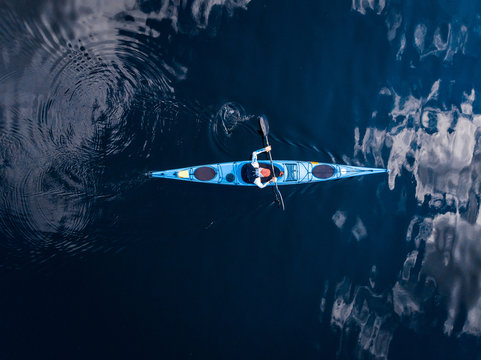Blue kayak with man sea, open space, aerial top view