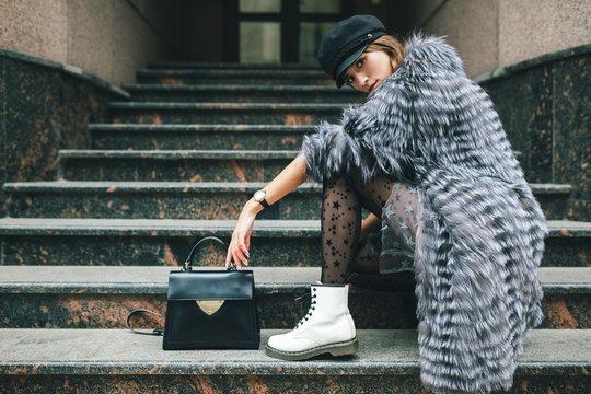 stylish woman in winter fur coat walking in street
