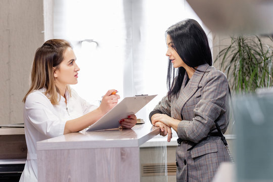 Client and doctor discuss cosmetic procedure in beauty clinic. Young stylish brunette girl makes appointment with beautician at reception with administrator. Concept anti-aging treatment and injection