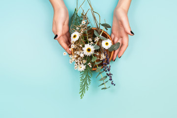 Photo sur Aluminium Spa Hands with herbs mix. Flat lay style. Modern apothecary concept