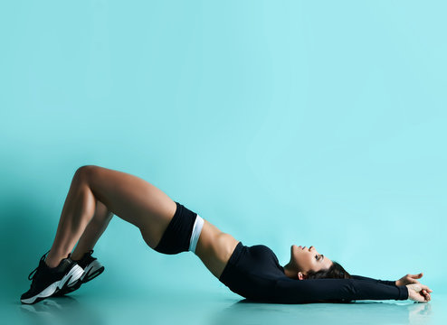 Fitness and diet concept. Young woman with athletic body and perfect buttocks is lying on her back doing exercises