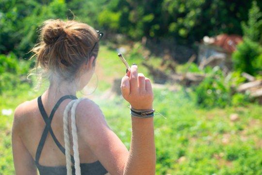 Female smoking a marijuana joint shot from behind