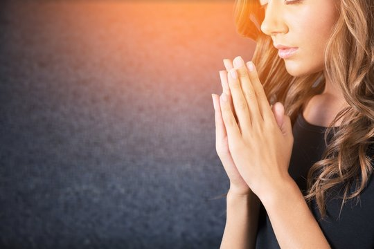 A young beautiful  girl prayed ion background
