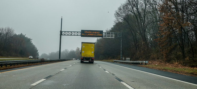 Electric warning sign over yellow box truck on highway warning of crash ahead and that all lanes are closed