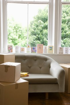 Moving Boxes By Sofa With Cards On Windowsill