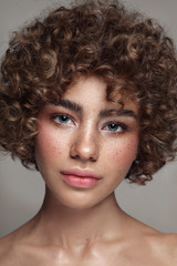 Portrait of young beautiful freckled girl with curly hair and clean makeup