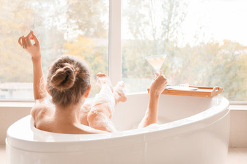 Beautiful young woman drinking cocktail while taking bath Fototapete
