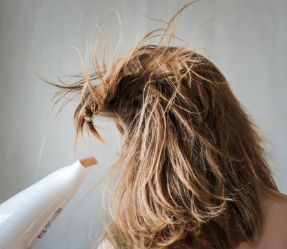 girl drying  her hair by a hair dryer