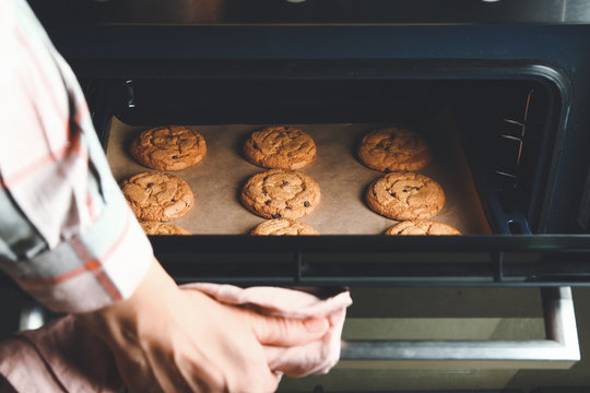 Woman taking baking tray with cookies out of oven