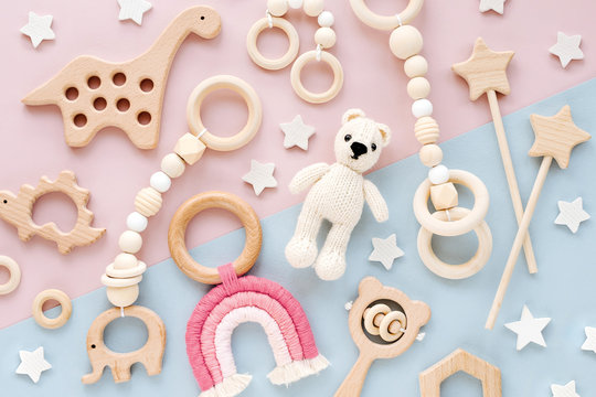 Cute wooden baby toys on pink and light-blue background. Knitted bear, rainbow, dinosaur toy, beads and stars. Eco accessories,  beanbag and teethers for newborn. Flat lay, top view