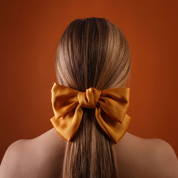 blond female hairstyle with color ribbon on orange wall background. close up of blonde girl head with carroty bow in her hair, rear view. fashion style photoshoot of woman in studio