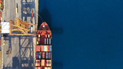 Aerial drone top down photo of industrial cargo container tanker ship carrier docked in commercial port terminal Fotomurales