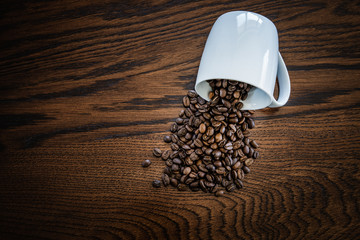 coffee beans on wooden background with white coffee cup. Cafe background concept