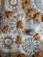 Gingerbread cookies with honey holding salted almond on wooden table with white powdered sugar sprinkled all over in shape of snow flakes. Rustic and delicate perfect for Christmas time and holidays.