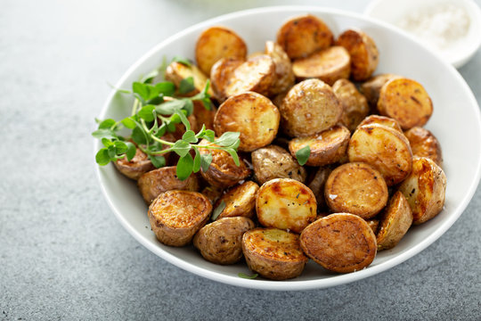 Roasted or air fryed baby potatoes with oil and herbs in a bowl
