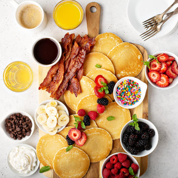 Big pancake breakfast table with berries, bacon and maple syrup