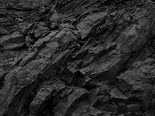 Black rock background. Dark gray stone texture. Black grunge background. Mountain close-up. Distressed backdrop.