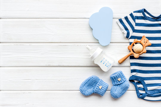 Newborn baby boy set - blue clothes as bodysuit, booties, toys - on white wooden table top-down frame copy space