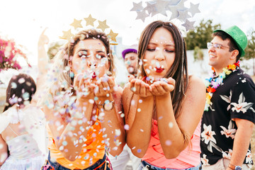 Foto op Canvas Carnaval Brazilian Carnival. Young women in costume enjoying the carnival party blowing confetti