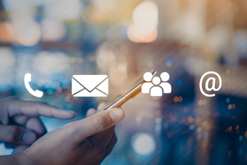Contact us or Customer support hotline people connect. Businessman using a mobile phone with the (email, call phone, mail) icons.