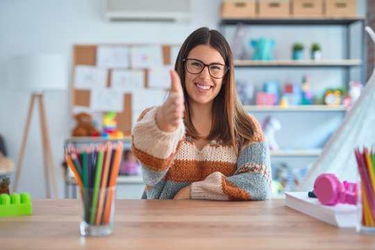 Young beautiful teacher woman wearing sweater and glasses sitting on desk at kindergarten smiling friendly offering handshake as greeting and welcoming. Successful business.