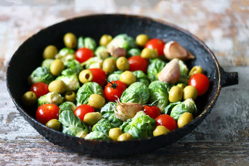 Poster Brussels Brussels sprouts with vegetables and herbs in a pan. Cooking Brussels sprouts. Vega food. Selective focus.
