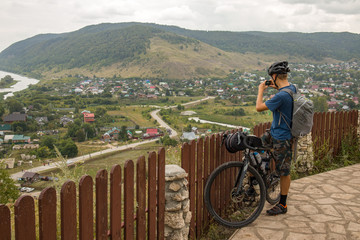 A traveler on a bicycle takes pictures of the local landscape.