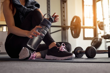 Woman holding water after fitness exercise at gym. Healthy and lifestyle concept.