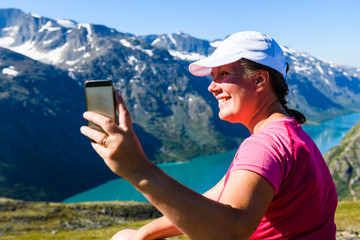 Woman taking picture of mountains