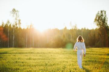 Woman walking in meadow Fotobehang