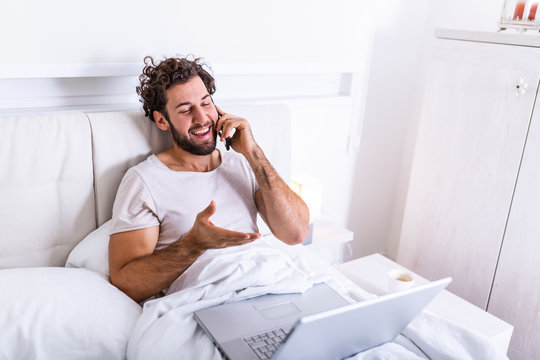 young businessman working happy and relaxed from bed with laptop computer using mobile phone in workaholic concept , Working from home in the morrning and drinking coffe