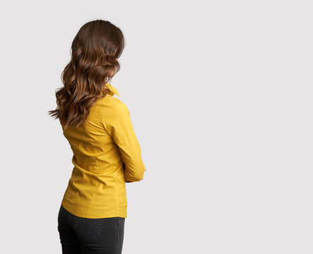 Back view of a business woman in yellow shirt is looking away