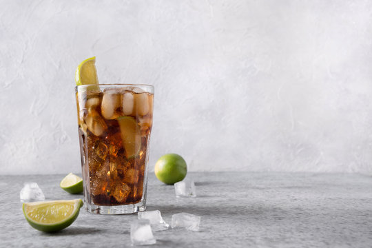 Cocktail Cuba Libre or long island iced tea with rom, cola, lime and ice in glass on grey stone table. Horizontal orientation.