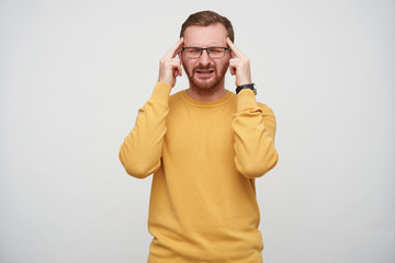 Stressed young brunette bearded guy in eyewear frowning his face with closed eyes, keeping forefingers on his temples while having strong headache, isolated over white background