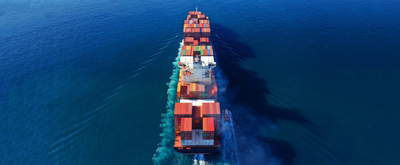 Aerial drone photo of industrial cargo container carrier cruising the open ocean deep blue sea Wall mural