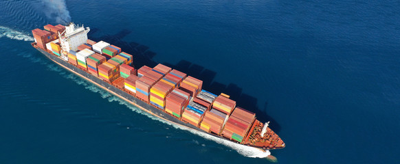 Aerial drone photo of industrial cargo container carrier cruising the open ocean deep blue sea - fototapety na wymiar