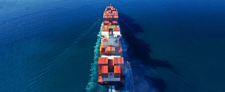 Aerial drone photo of industrial cargo container carrier cruising the open ocean deep blue sea