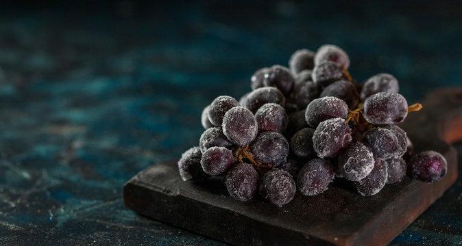Frozen Black ripe grape for dessert on black background.