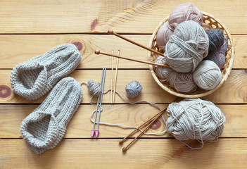 Rustic still life with handmade knitted warm slippers and accessories for knitting: balls of woolen yarn in woven basket, hooks, knitting needles on a wooden background. Flat lay, close-up, top view