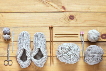 Top view of handmade knitted warm slippers and accessories for knitting: hooks, needles, balls of woolen yarn on wooden background. Still life.  Knit concept. Place for text. Flat lay, copy space